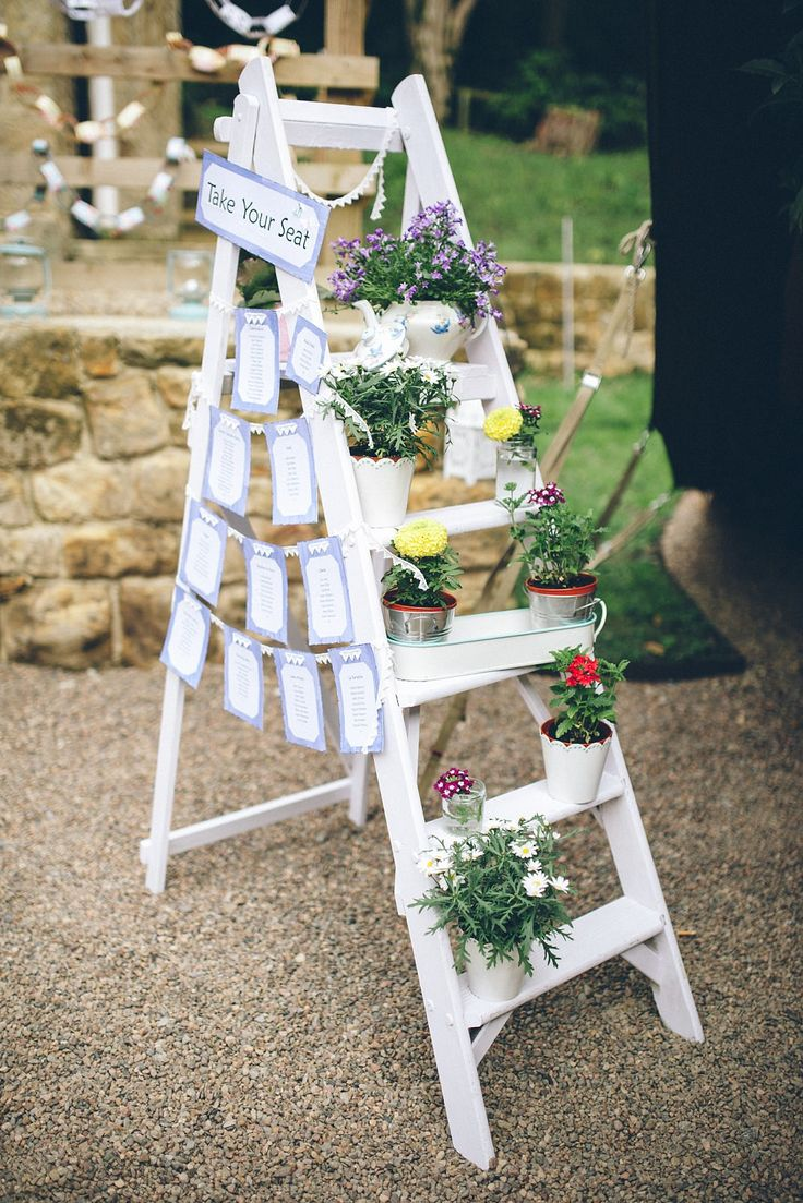 White Vintage Step ladder with stung up stationery and potted plants on the steps -   Image by Paul Santos - Geneva Maggie Sottero lace wedding dress & Ted Baker tweed suit with pastel colour scheme at an outdoor countryside Tipi wedding