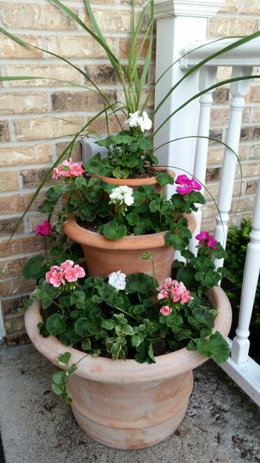 Stacked planters and geraniums that my kids made me for mothers day after seeing a similar pin on one of my boards.