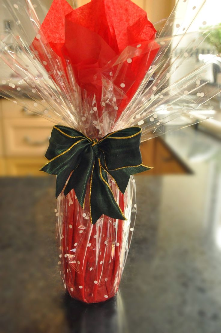 http://giftwrappingcourses.co.uk create a stunning bottle wrap with red tissue paper and a clear dotted cellophane.