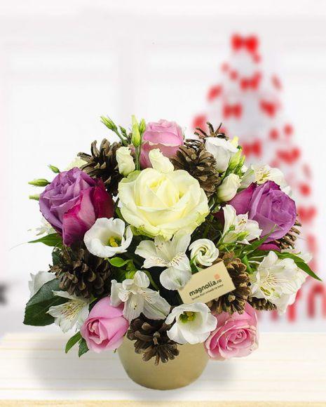 Un aranjament feminin în care rozul şi albul se îmbină perfect, florile şi accesoriile de iarnă făcându-l absolut deosebit. Combinaţia de specii şi de culori creează un aranjament delicat, potrivit a fi oferit doamnelor sau domnişoarelor