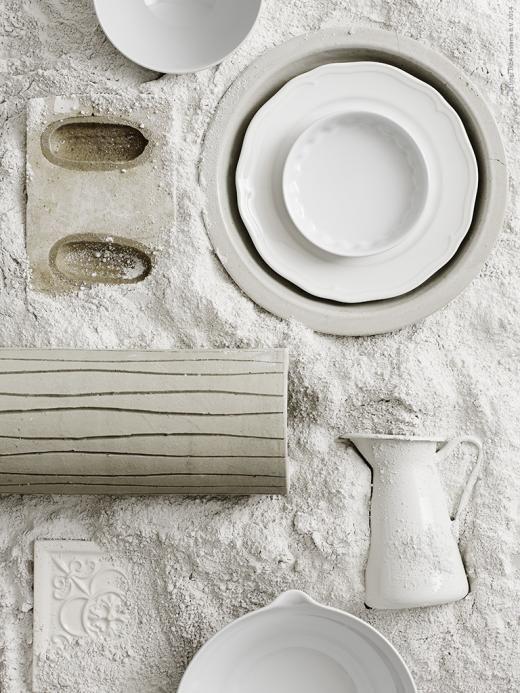 Mjölkvitt! Assietten ARV med sin snirkliga dekorativa kant dukas lager-på-lager i olika nyanser av mjölkvitt. Kannan SOCKERÄRT sticker upp ur gipspulvret tillsammans med vasen FREDLÖS som påminner om en pelare.