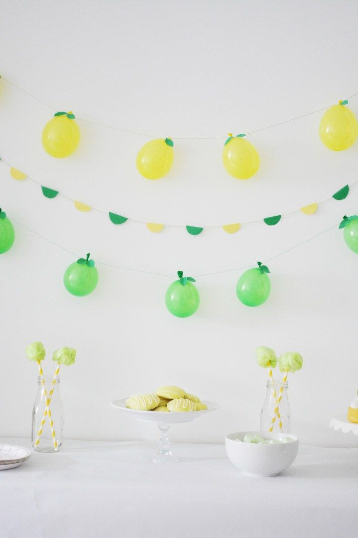 It was only a matter of time before we turned the fruity balloon straw concept into other party projects! Turns out they make for perfect mini fruit garlands!  Looking at these now I wish I had done more balloons so the look was a little fuller but I still like these little lemons and limes! Materials Water balloons // Balloon pump // String // Tape // Scissors // Green cardstock // Leaf templates   1. Use the balloon pump to blow up your yellow and green water balloons. 2. Tie the string…