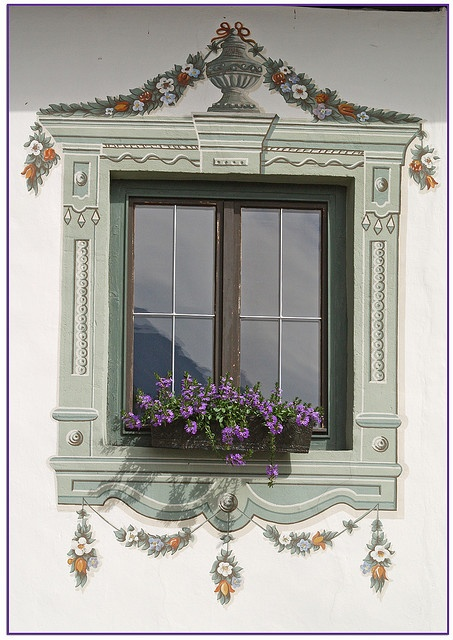 Creative collage of mural window and actual windowbox with silk flowers.