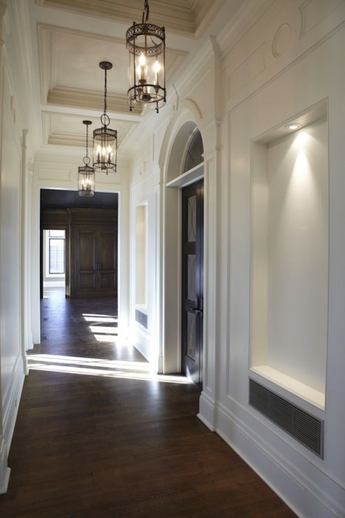 Traditional hallway with lit hallway niches and coffered
