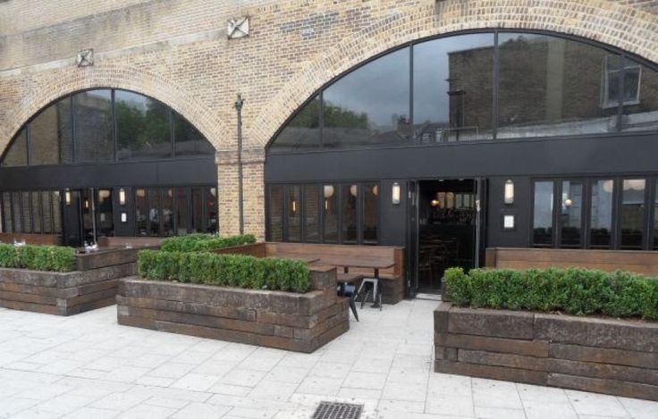 Raised beds/built-in benches from railway sleepers at pub in Hoxton