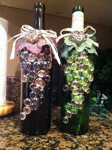Recycled wine bottle, christmas lights, glass gems, grape leaves, and a raffia bow.