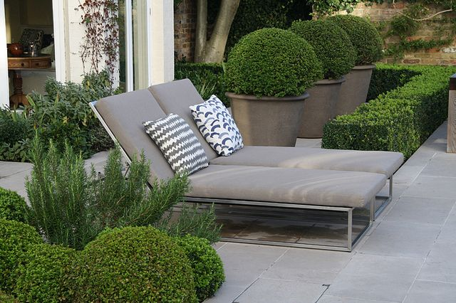 Formal Structural Garden | Contemporary recliner chairs on raised stone terrace | Charlotte Rowe Garden Design