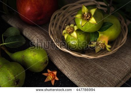 Green pomegranate in basket and fruits closeup background, dark photography.