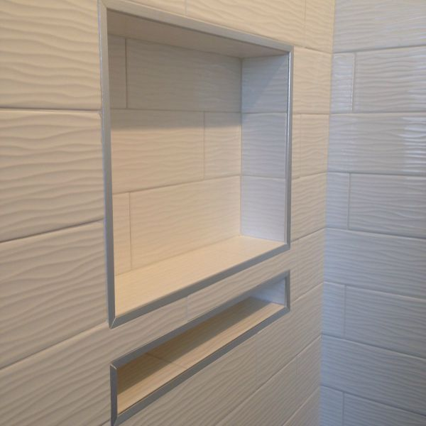 The master bathroom was no prize either…it was tight and there was nothing grand about it.  Relocating the toilet in the adjoining bath to the opposite wall allowed us to widen the shower in this bath by nearly 2 feet which made a HUGE difference.  I found this glossy white 2 x 6 subway tile with a wave pattern on it which I wanted to use immediately.