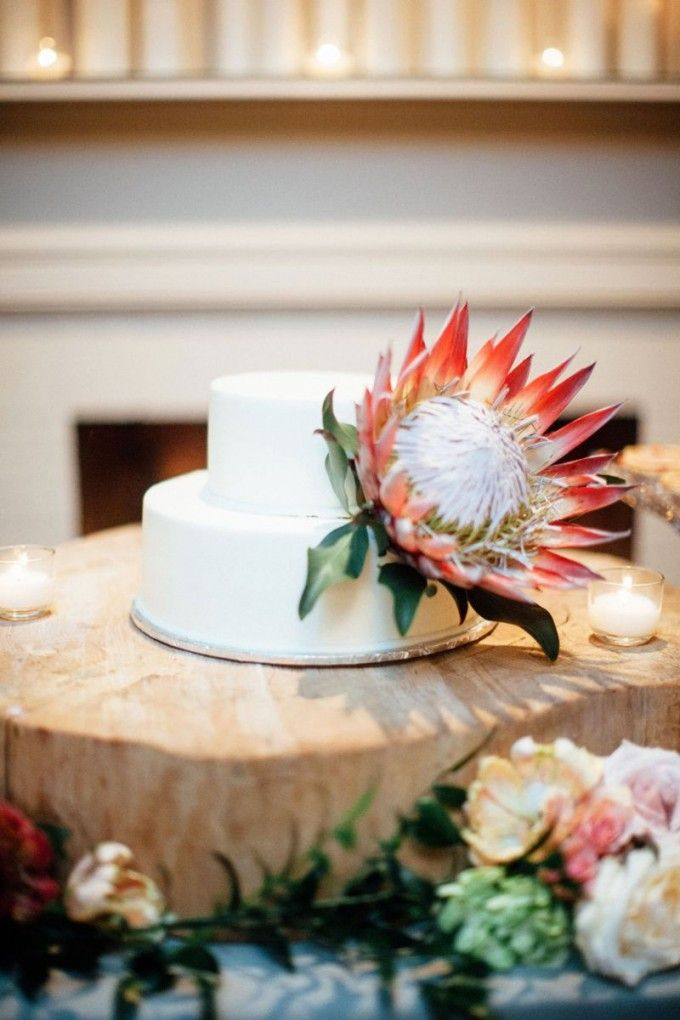 Statement Blooms like the King Protea deserve a minimalistic white cake like this one! Absolute perfection! #cedarwoodweddings   Navy and Blush Cedarwood Destination Wedding   Cedarwood Weddings