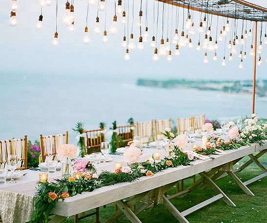 Love this idea of trailing flowers and greenery along the length of the back of the tables. Leaves room for table settings and share platters.