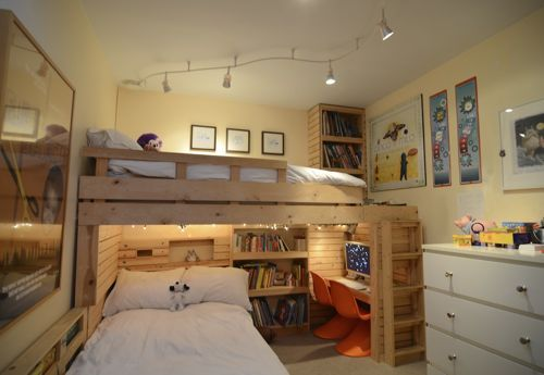 Great use of space in a bedroom for three boys - loft bed, built in desks, bookshelves, and toy storage