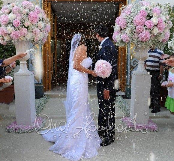Una pioggia di riso accoglie gli sposi all'uscita della chiesa vestita di delicate sfumature di rosa.