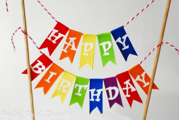 To make the happy birthday bunting, simply tape pieces of ribbon onto baker's twine and add scrapbook sticker letters to the ribbon. Then tie the twine to 2 bamboo skewers and insert into the cake – easy as that!