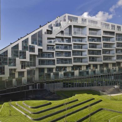 """8 House: Location: Copenhagen, Denmark Architect: Bjarke Ingels  8 House is a large mixed-use development built in the shape of a figure 8 on the southern perimeter of the new suburb of Orestad in Copenhagen, Denmark. The bow-shaped building consists of 61,000 square metres of three different types of residential housing and 10,000 square metres of retail premises and offices. Bjarke Ingels explains the design, """"that by mixing traditional ingredients, retail, rowhouses and apartments in…"""