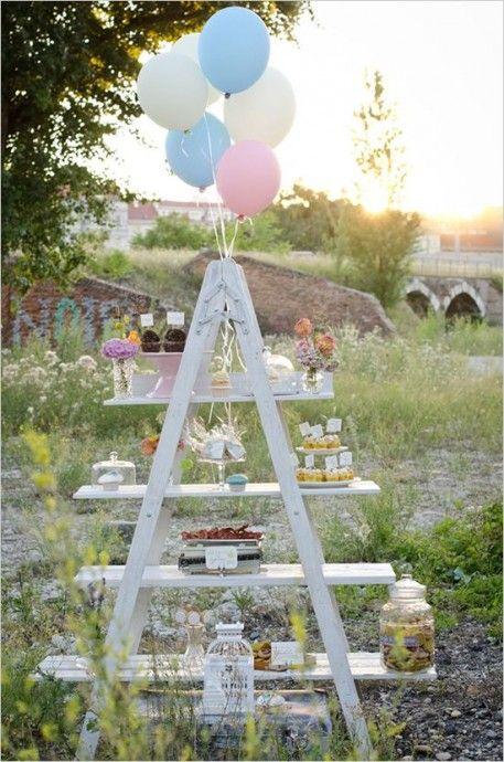 Et si votre échelle servait de sweet table ? Quelle bonne idée ! Peignez-là d'une teinte pastelle, accrochez-y quelques ballons et disposez sur des planches glissées entre les marches quelques douceurs ou bonbons pour satisfaire la gourmandise de vos convives.