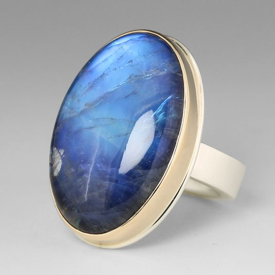 Ancient Romans believed moonstone was born from solidified rays of the moon, an idea that is perfectly captured in this Jamie Joseph rainbow moonstone ring. The vertical smooth oval moonstone is set in a 14k yellow gold bezel on a sterling silver