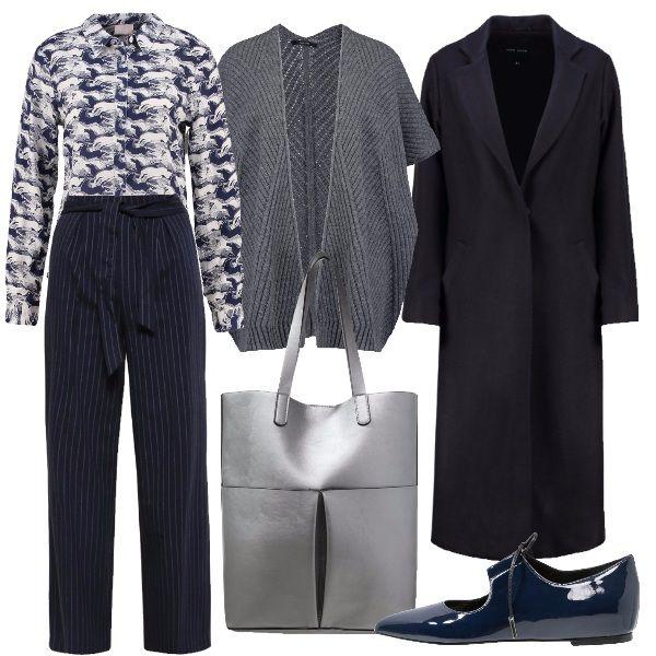 Camicia fantasia su pantalone gessato, la mantella grigia per tenere caldo in ufficio o a lezione e il cappotto per fare completo. Capiente la shopper metallizzata e femminili le stringate di vernice.