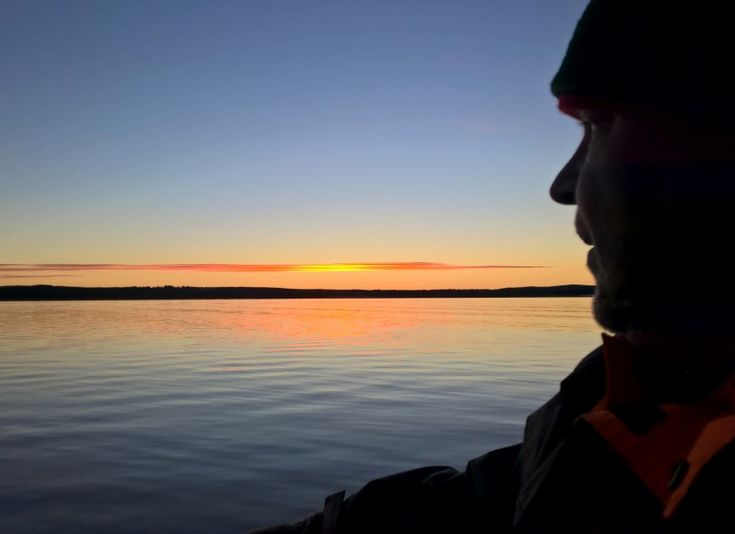 Fisherman admiring the midnight sun at the Arctic Circle in Miekojärvi in Lapland