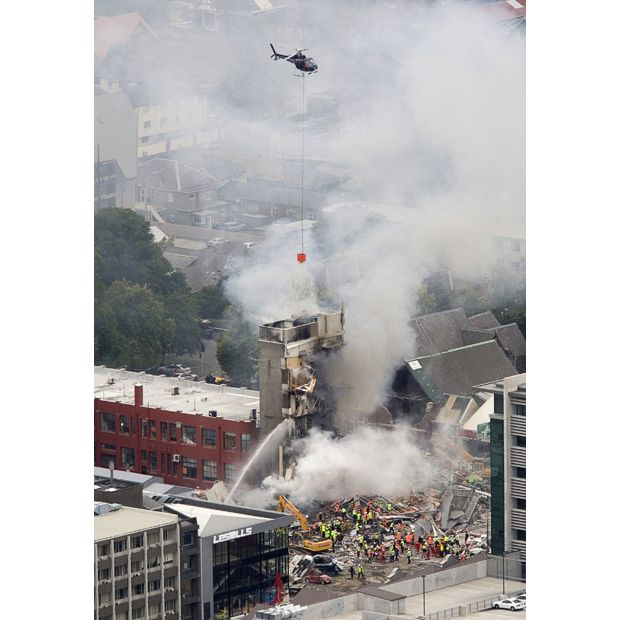 Rescue workers and a helicopter work to extinguish a fire at a collapsed building in central Christchurch, New Zealand after the earthquake