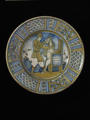 Dish, made in Deruta, c. 1556. A man is washing a donkey's head. The text on the chair, on which the donkey is seated, reads: 'Chi lava el capo al aseno se perd o,' 'who washes the head of an ass wastes his efforts.'