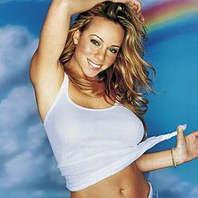 A woman with blond hair is smiling. She wears a short white shirt and soft make-up. She crosses her right arm behind her head and is pulling a portion of her shirt with her left hand. She is standing in front of a wall with a cloud and a rainbow on it.