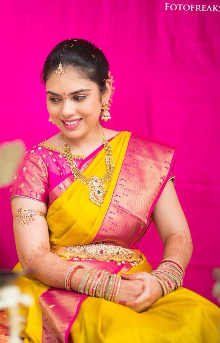 South Indian bride. Gold temple bridal jewelry. Jhumkis.Yellow Silk kanchipuram sari with boat neck contrast pink blouse.Braid with fresh jasmine flowers. Tamil bride. Telugu bride. Kannada bride. Hindu bride. Malayalee bride.Kerala bride.South Indian wedding