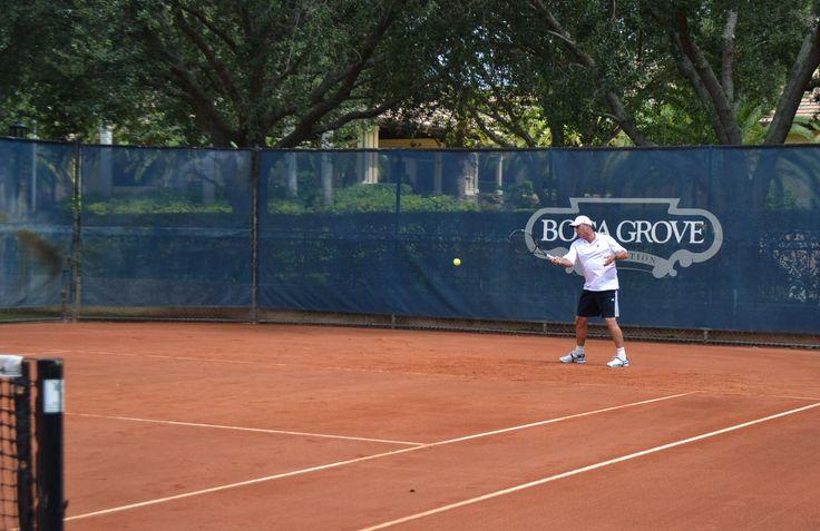 Tennis legend, Ivan Lendl, volleying some balls at Boca Grove's red clay stadium court.