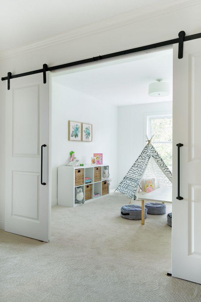 Flex room playroom with barn doors. The landing area opens to a flex room, currently used as a playroom. Bria Hammel Interiors