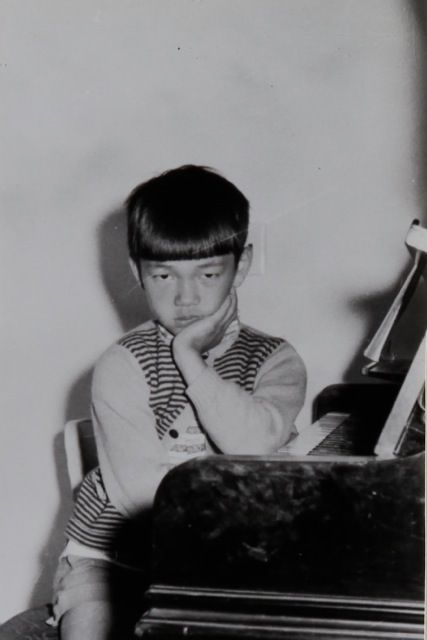 Ryuichi Sakamoto (7 years old) at home with a piano, 1959.