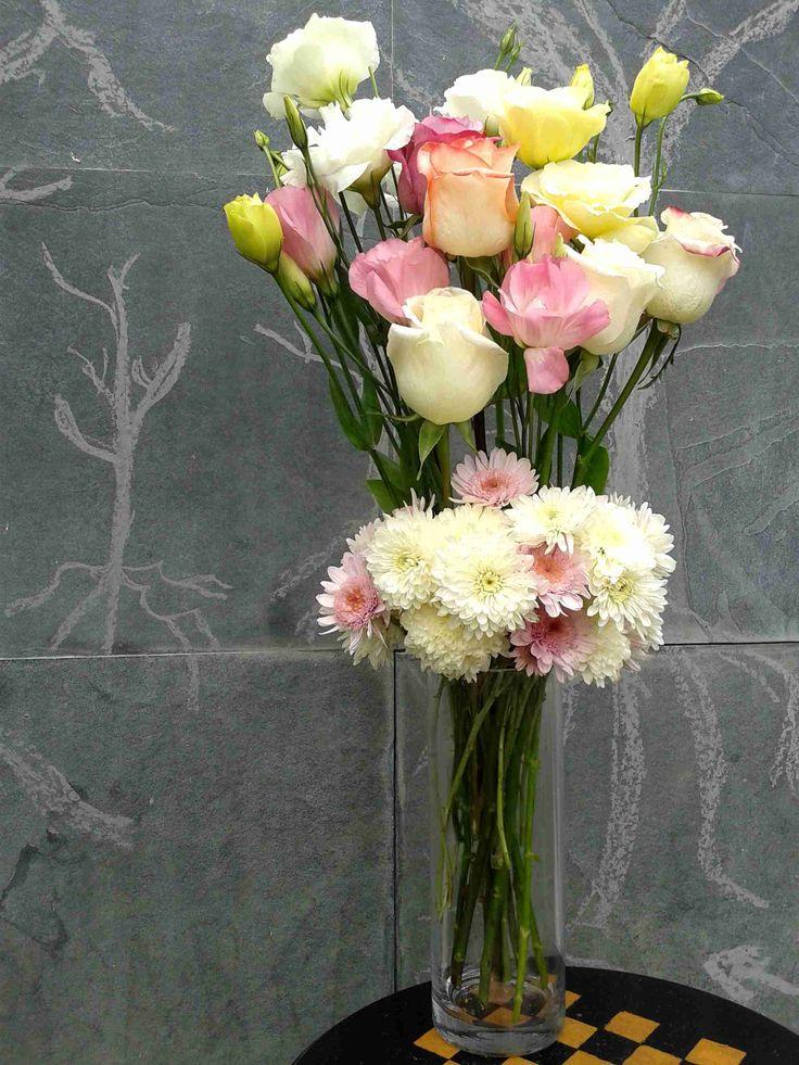 Arreglo floral de rosas, lisianthus y crisantemos en florero cilindro.