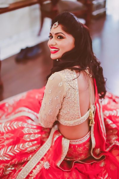 light gold and red lehenga, gota patti work, gold maangtikka, half tied hair, candid photo , blouse back style, cutout back, red lipstick, front puff hairstyle for engagement,