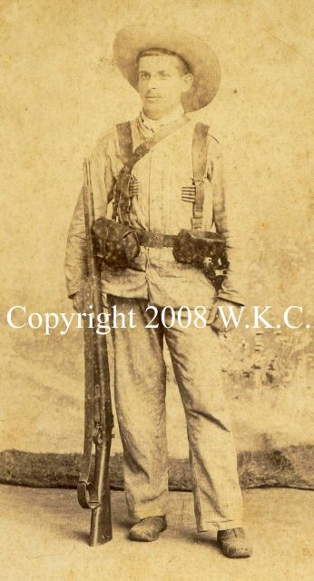 """This image illustrates the typical Spanish soldier on campaign that Americans would face in the fight for Santiago. He is dressed in a Guayabera pattern tunic and trousers of rayadillo. His jipijapa straw hat is standard for the tropics. The accoutrements are Model 1886 pattern with some improvements for the Mauser rifle he carries. This equipment is made of black leather with a brass belt plate embossed with the regimental number """"43""""."""