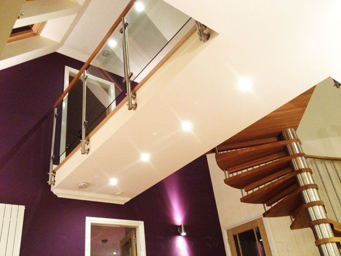 Stunning spiral stair with solid oak treads and handrail.  Landing balustrade with glass infill panels.