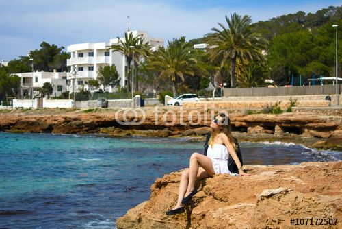 Young classy girl sitting on rocky coast of the ibiza island during hot summer