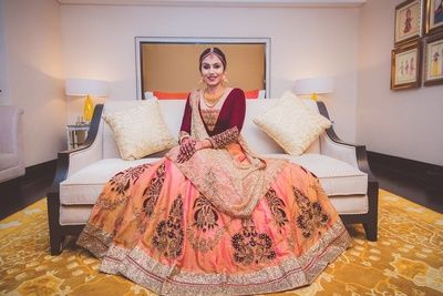 Sangeet Lehengas - Bride in a Coral and Marsala Lehnga with a Beige Dupatta | WedMeGood #wedmegood #indianbride #indianwedding #bridal #lehenga #marsala #coral #gold #bronze #sangeetlehenga #engagementlehenga