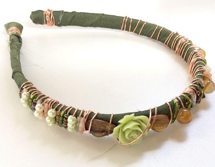 Tiara+de+plástico+1cm+de+largura.+Encapada+com+tiras+de+seda+(sari+silk+)+na+cor+verde+musgo.+Trabalhada+a+mão+com+arame+importado+(copper+wire+)+na+cor+rosê.+Possui+pedras+brasileiras,+cristais+swarovski+,+murano+,+miçangas+,+entre+outros.+<br>Modelo+exclusivo+.