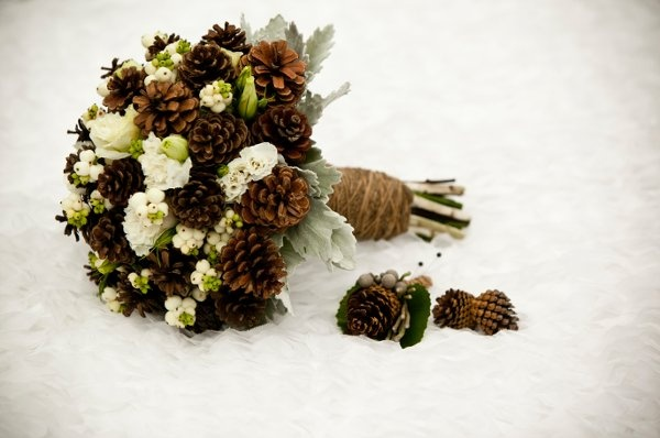 For a winter themed photo shoot featured in WeddingsInWinnipeg.ca, we created this stunning textural bouquet and matching boutonnieres with white roses, lisianthus, snowberries, dusty miller, and pine cones. A bit of twine on the handle finished it all off! Photo by Mike Tinholt Photography