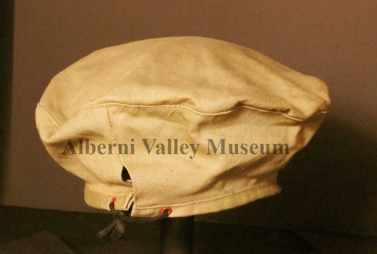 Light green cloth hat. Somewhat like a tam, except for the addition of a piece of cloth between the thin head band and the circular top. The hat may be puffed up, draped and manipulated into the desired shaped. There is a tie closing at back.  [Alberni Valley Museum Collection 1971.84.1e]