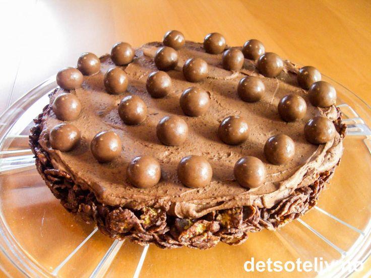 """Dette er en slik type """"godterisjokoladekake"""" som jeg egentlig hadde tenkt å ta med i barnehagen til datteren min. Men neimen om jeg fikk lov til det etter at mannen min hadde smakt sin første bit og overraskende nok falt pladask. """"Cornflakessjokoladekake"""" består av en bunn laget av cornflakes og smeltet sjokolade. Bunnen dekkes med luftig sjokoladefløtekrem og pyntes med sjokolade- og hasselnøttkuler. Det er ikke ofte at en hel kake blir spist opp av bare mannen min og meg..."""