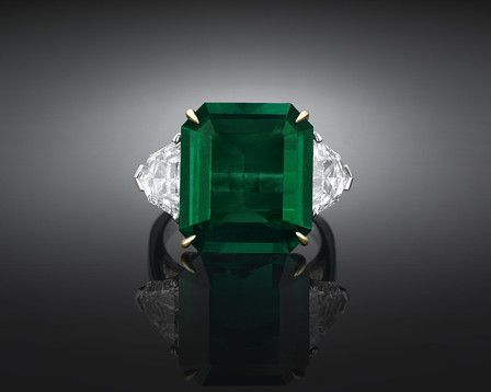 This outstanding, Natural Colombian emerald boasts the perfect, verdant hue Weighing 9.28 carats, this rare gem is supported by two shield-shaped white diamonds This stunning emerald is certified as having no treatment to enhance its clarity All gems are set in platinum and 18K gold $495K