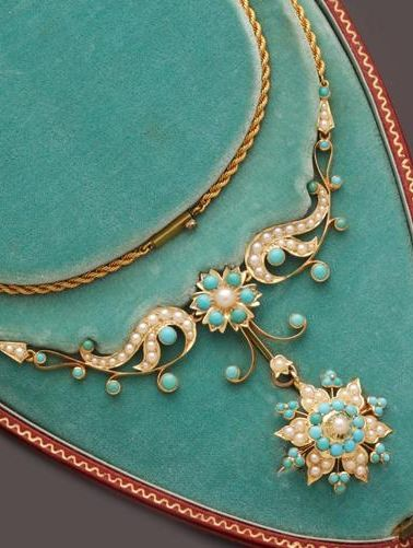 An early 20th century turquoise and half pearl necklace. Suspending a turquoise cabochon and half pearl snowflake cluster pendant, with detachable brooch fitting, from similarly set scrolled panels, to a ropetwist-link back chain.