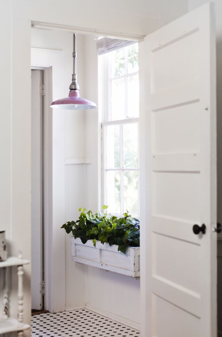 White-washed hallway with pastel pendant lighting and window foliage.