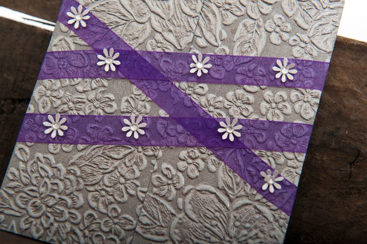 Metal look embossed paper in a gate fold style invitation, closed with purple organza ribbon and tiny white flowers with diamante centers.
