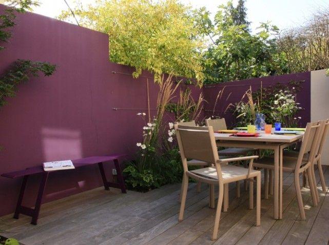 Le concept est simple mais efficace : une terrasse en ipé, comme une estrade, prolongée sur deux côtés par une bande de terre pour accueillir un jardin miniature, et surtout un parti pris de couleur avec des murs peints en aubergine et en muscade, ainsi qu'un mobilier dans les mêmes tons.