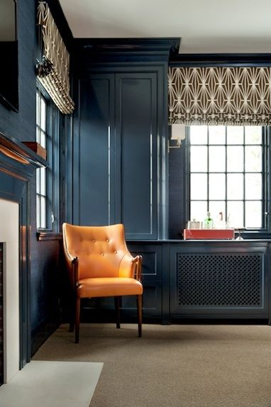 dark walls contrasted with a bright furniture piece and patterned curtains