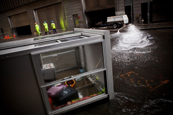 NEW YORK, NY - OCTOBER 30: Con Edison employees monitor the drainage of water being pumped out of Seven World Trade Center, caused by Hurricane Sandy, on October 30, 2012 in the Financial District of New York, United States. The storm has claimed at least 16 lives in the United States, and has caused massive flooding accross much of the Atlantic seaboard. (Photo by Andrew Burton/Getty Images)