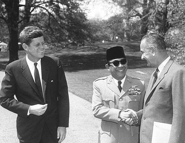 President of IndonesiaSukarno(sometimes known as AchmedSukarno, 1901 - 1970) (center) shakes hands with US Vice PresidentLyndon Johnson(1908 - 1973) as PresidentJohn F. Kennedy(1917 - 1963) smiles, Washington DC, April 25, 1961.
