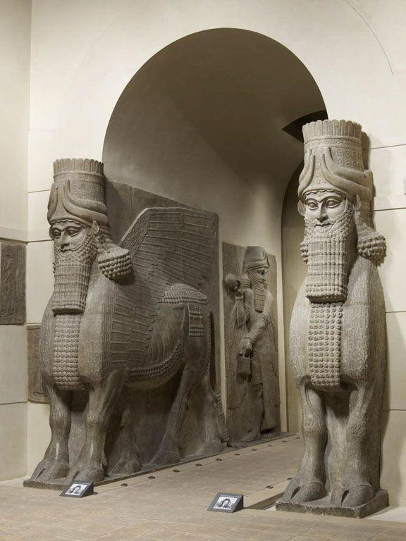 TDO 5 - Taureau androcéphale ailé ou Lamassou  Epoque néo-assyrienne, règne de Sargon II (721-705)  Façade m, porte k, Khorsabad, antique Dur-Sharrukin, Assyrie, Iraq Haut-relief et ronde-bosse, albâtre gypseux H. : 4,20 m. ; L. : 4,36 m. ; Pr. : 0,97 m. Paris, mdL.