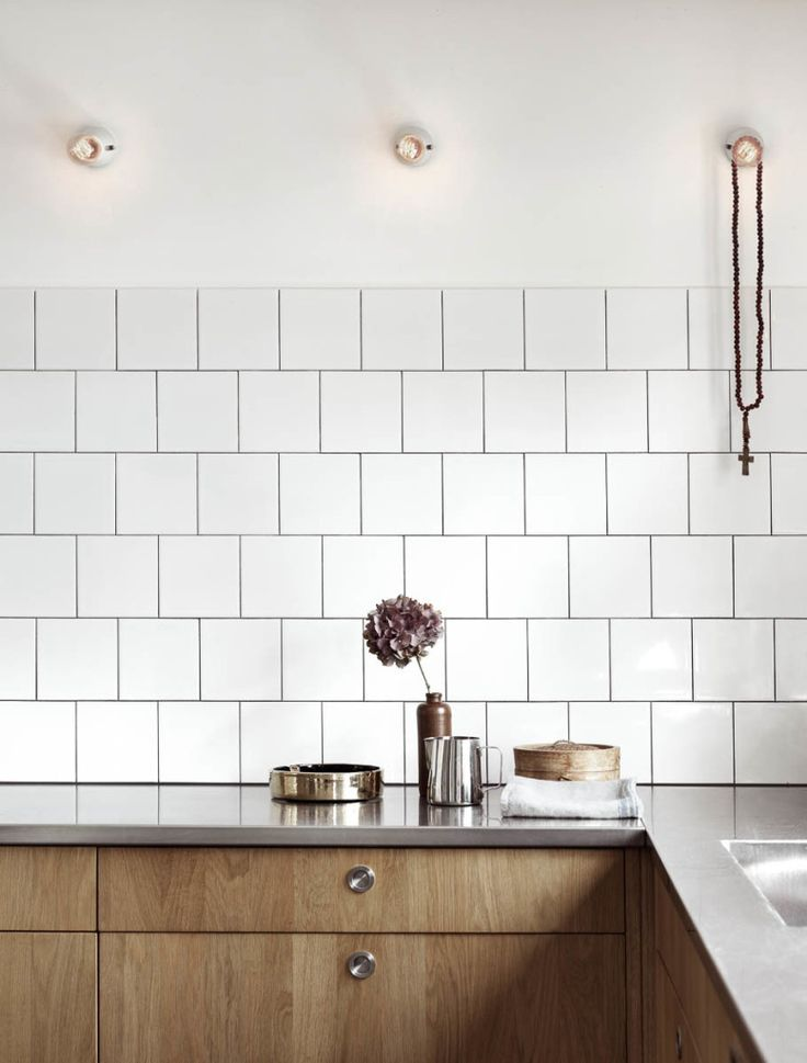 wooden kitchen cabinets. white square tiles with black grout